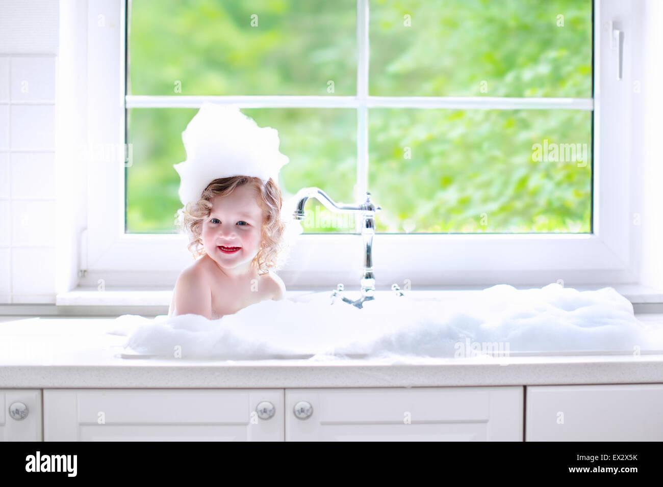 Child taking bath. Little baby in a kitchen sink washing hair with ...