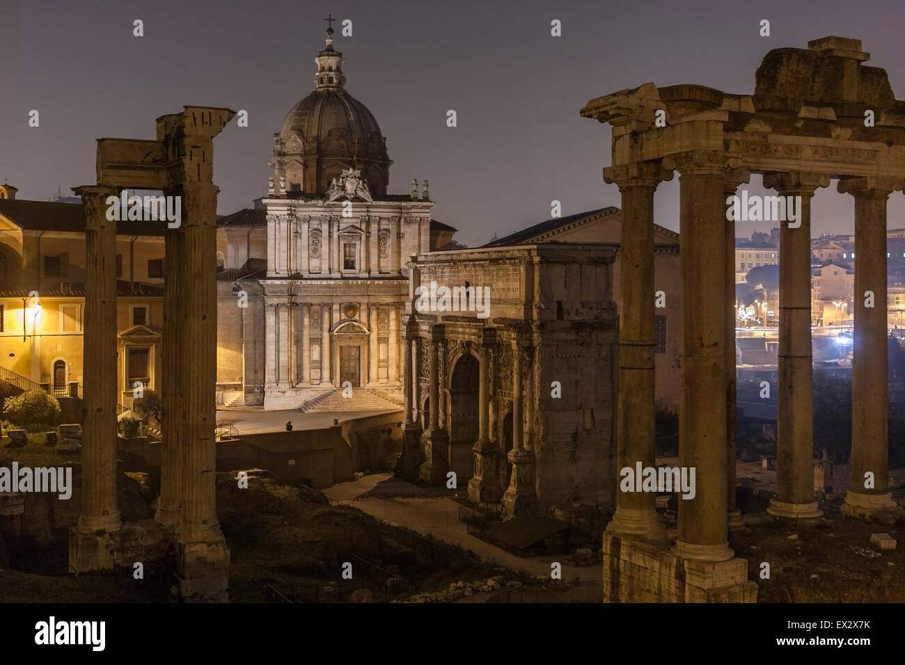 Foro Romano and Ruins of Septimius Severus Arch and Saturn Temple in Rome at night - Stock Image