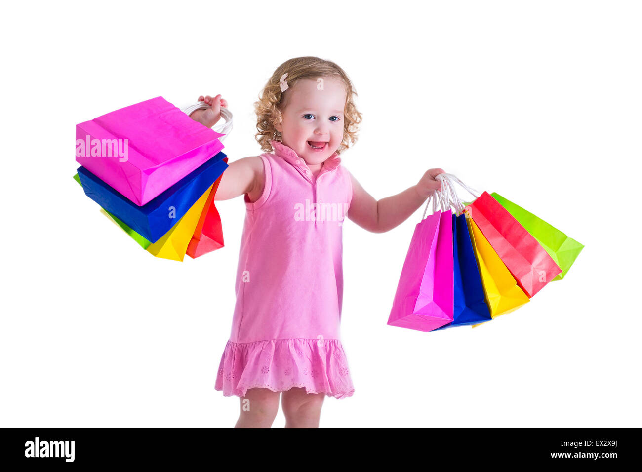 7d464a7bd Little girl in a pink dress holding colorful shopping bags. Child in a shop  buying clothes. Sale in a store. Kids with purchase