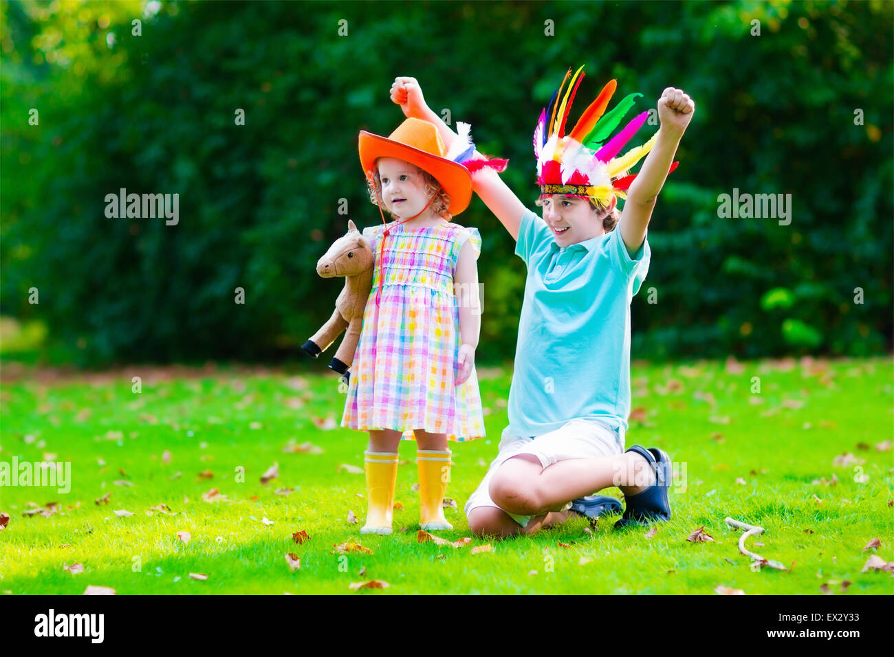 Kids in cowboy and cowgirl costumes playing outdoors. Children play with toy horse. Boy in Native American hat on - Stock Image