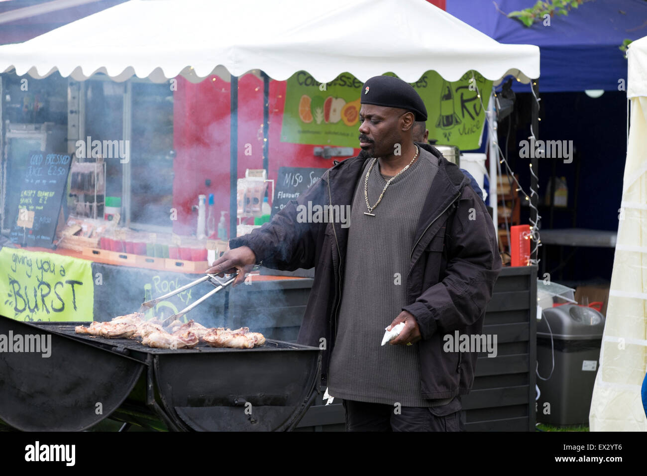 Afro Caribbean African Man Cooking BBQ Chicken - Stock Image
