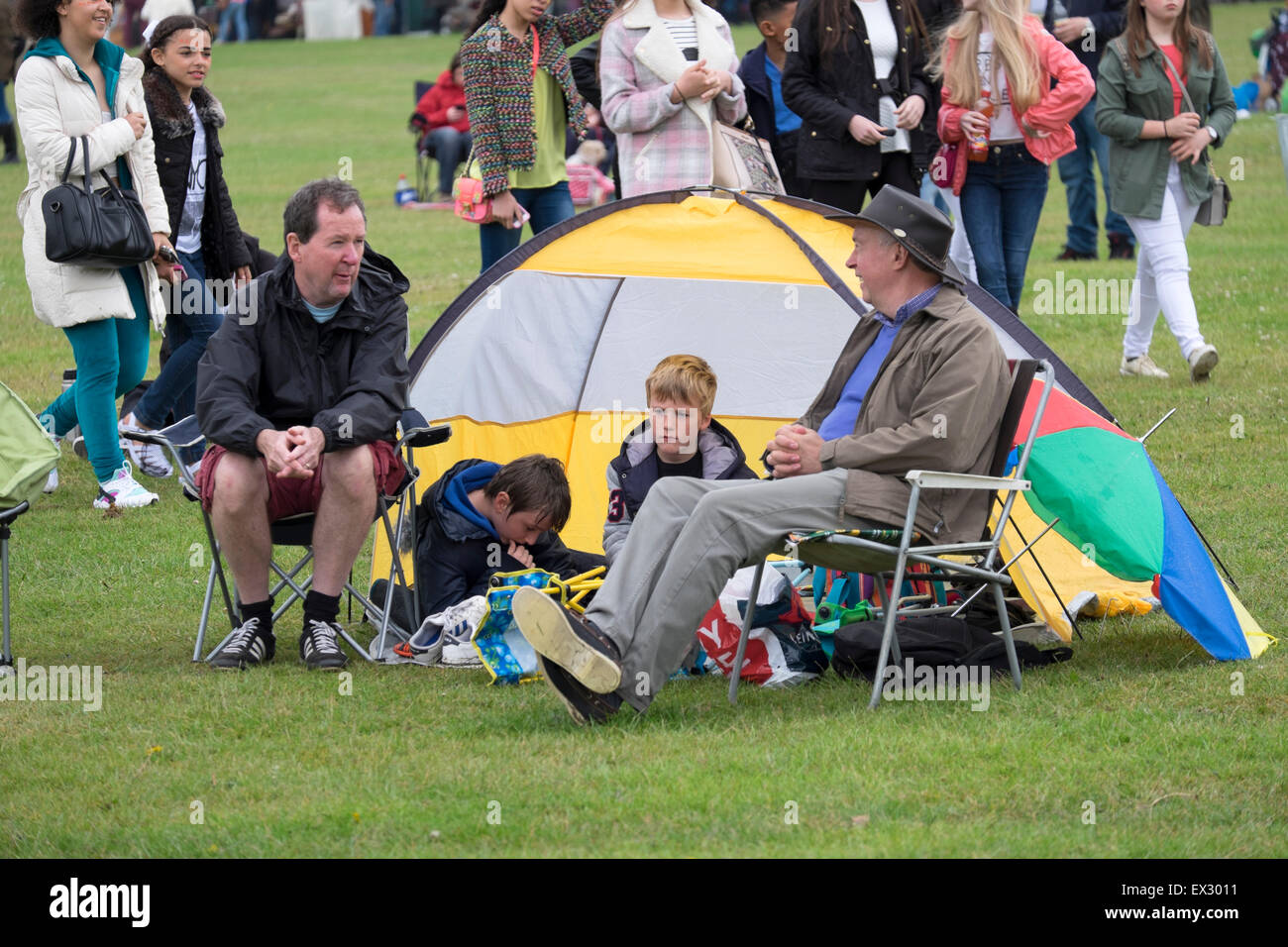 Family with Tent Watching Music Festival Damp Wet - Stock Image