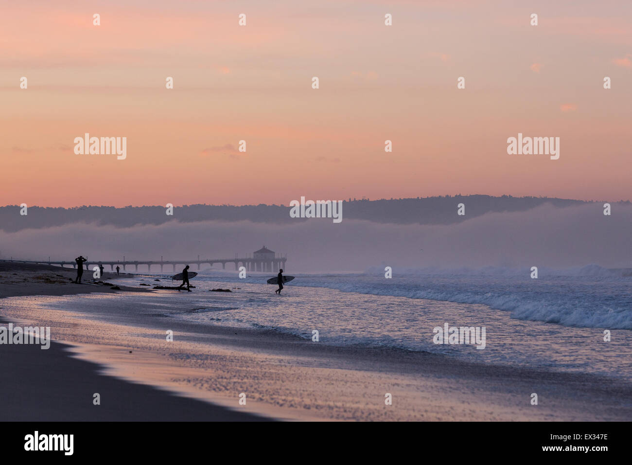 Surfers walk into the ocean under purple clouds in Manhattan Beach, California. - Stock Image