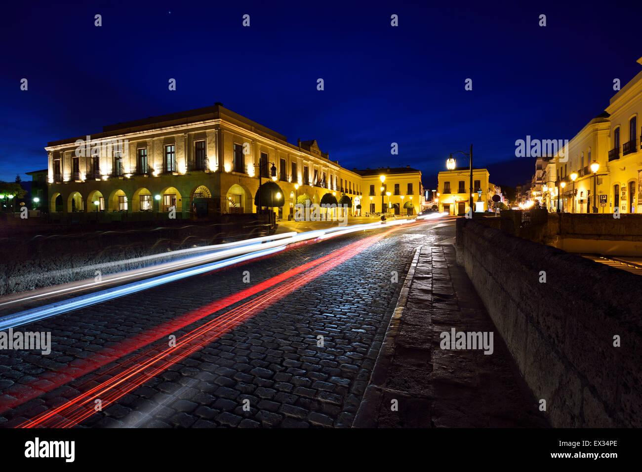 Indigo sky and car lights over Plaza Espana and Puente Nuevo bridge at dusk in Ronda Spain - Stock Image