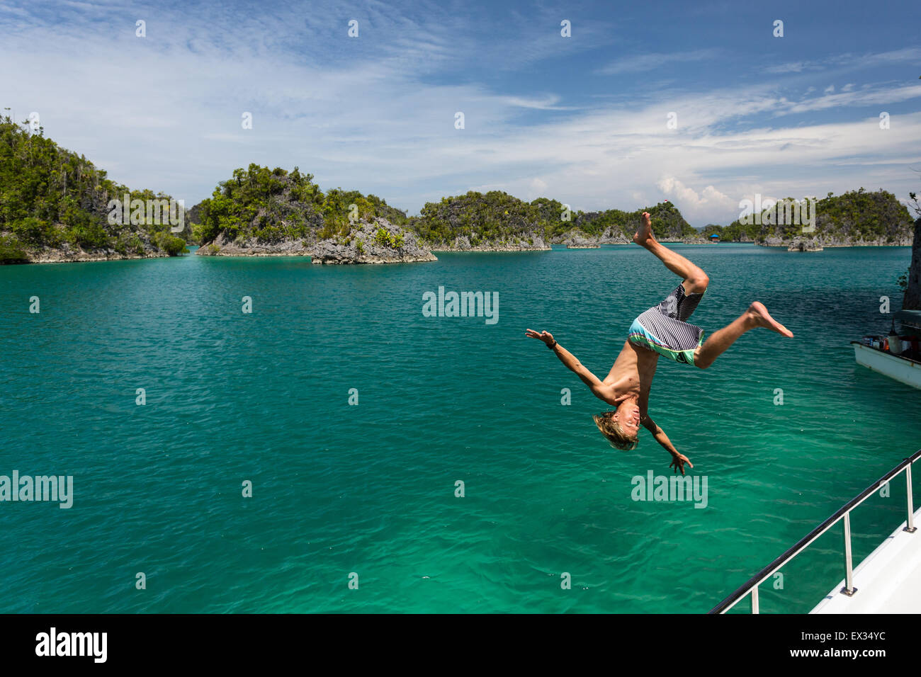 A young man does a flip off a boat in Raja Ampat's Fam Islands. - Stock Image