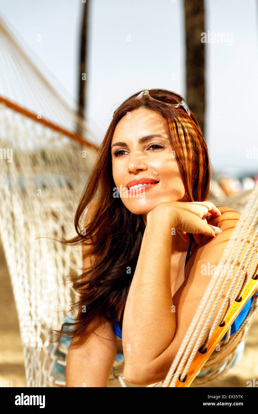 Low Angle Portrait View of a Woman Relaxing on a Beach in a Hammock with   Head Resting on One of Her Hand, San - Stock Image