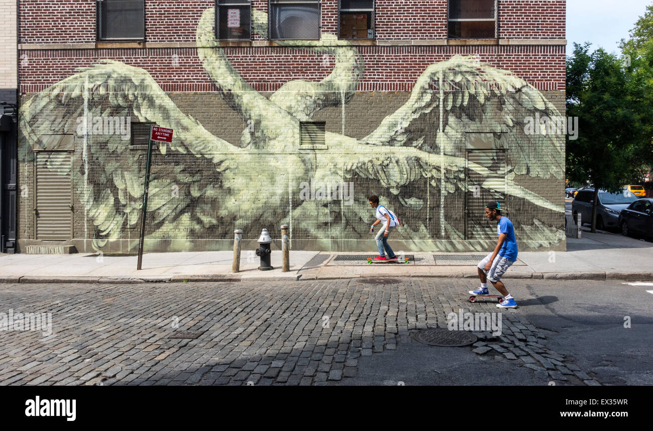 A young multi-racial couple skateboarding passed a large street art mural of mating swans, Lower East Side, New - Stock Image