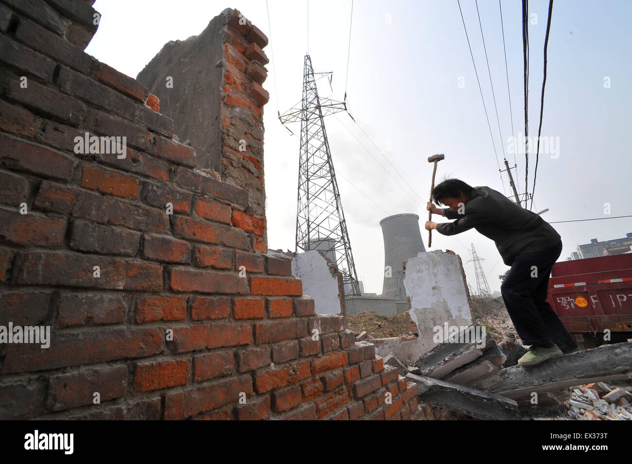 A labourer recycles usable steel bars at a demolition site in Xiangfan, Hubei province April 9, 2010.  VCP - Stock Image