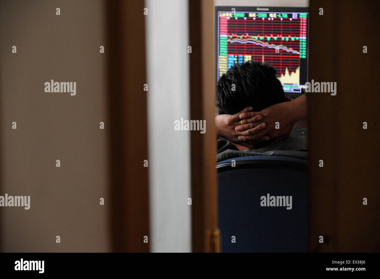 An investor gestures in front of an electronic board with stock information at a brokerage house in Taiyuan, Shanxi - Stock Image