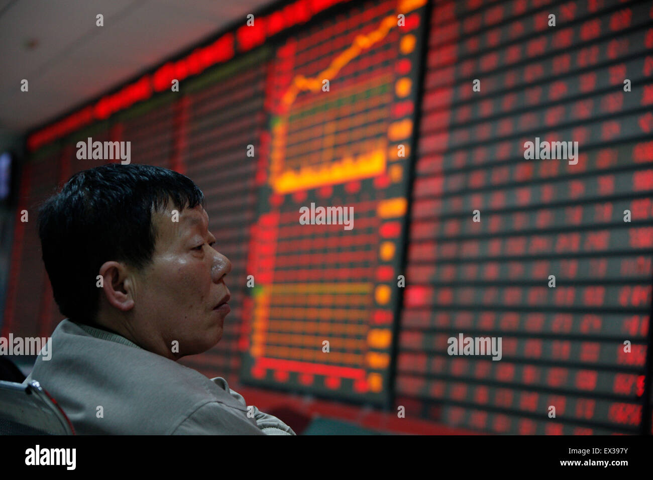 An investor gestures in front of an electronic board with stock information at a brokerage house in Huaibei, Anhui - Stock Image