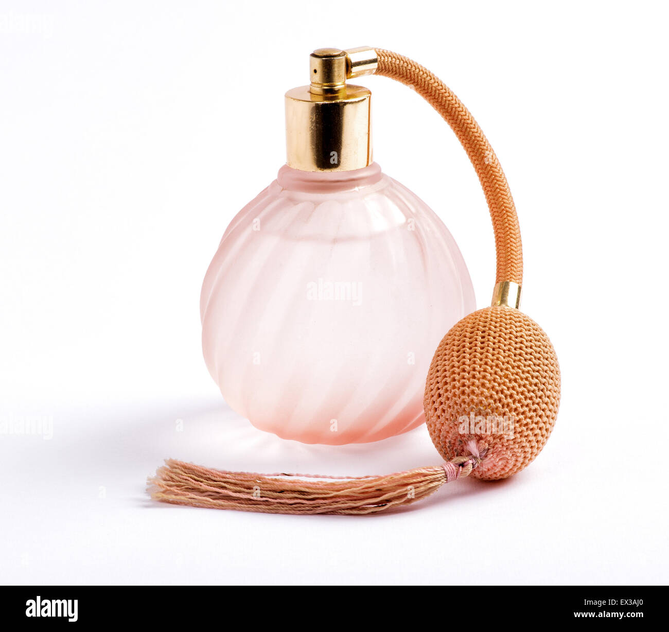 Classic perfume bottle with an atomizer pump for spraying the scent with attached long tassel in ridged swirling - Stock Image