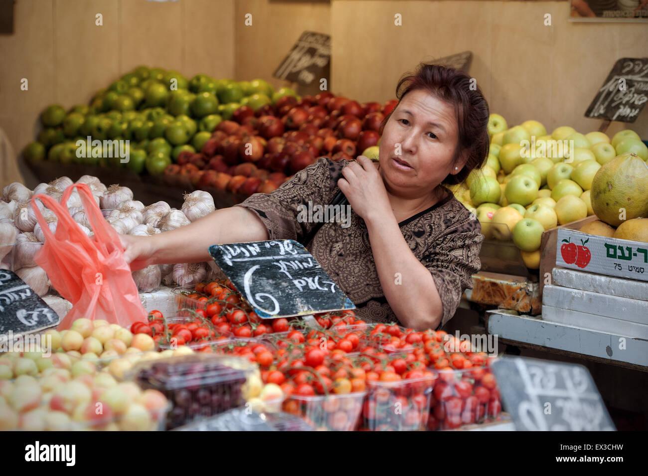 An adult woman shopping for produce at Mahane Yehuda, Jerusalem, Israel - Stock Image