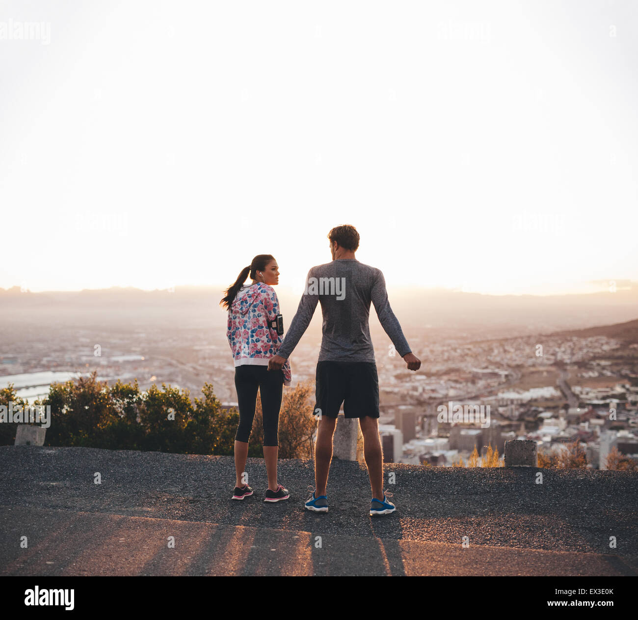 Rear view of a young couple standing together at sunrise. Joggers on hillside in morning. - Stock Image