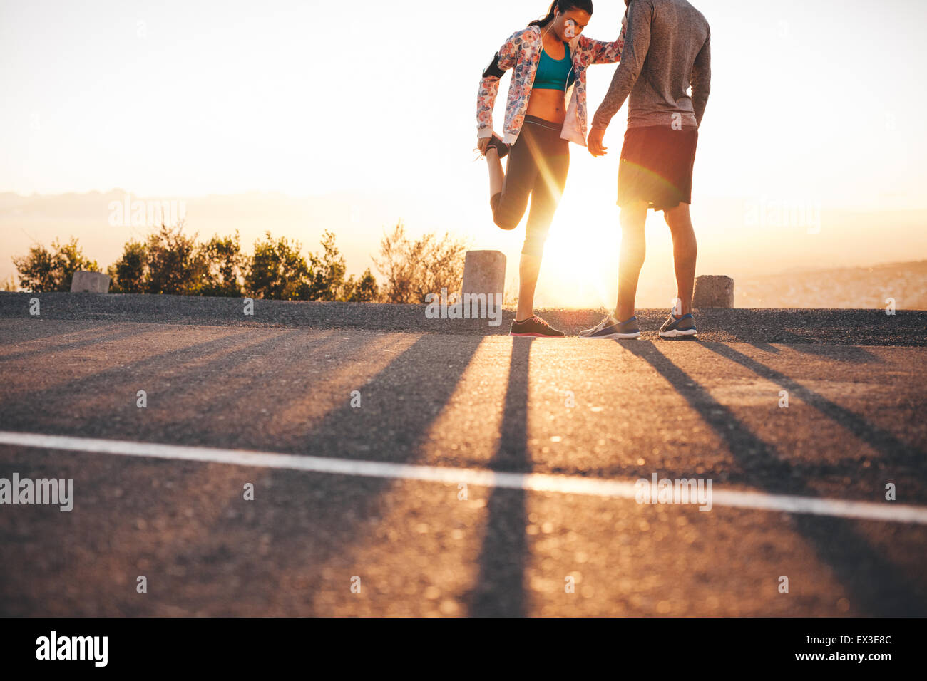 Outdoor shot of young joggers stretching before a run in morning. Young man standing and woman stretching her legs - Stock Image