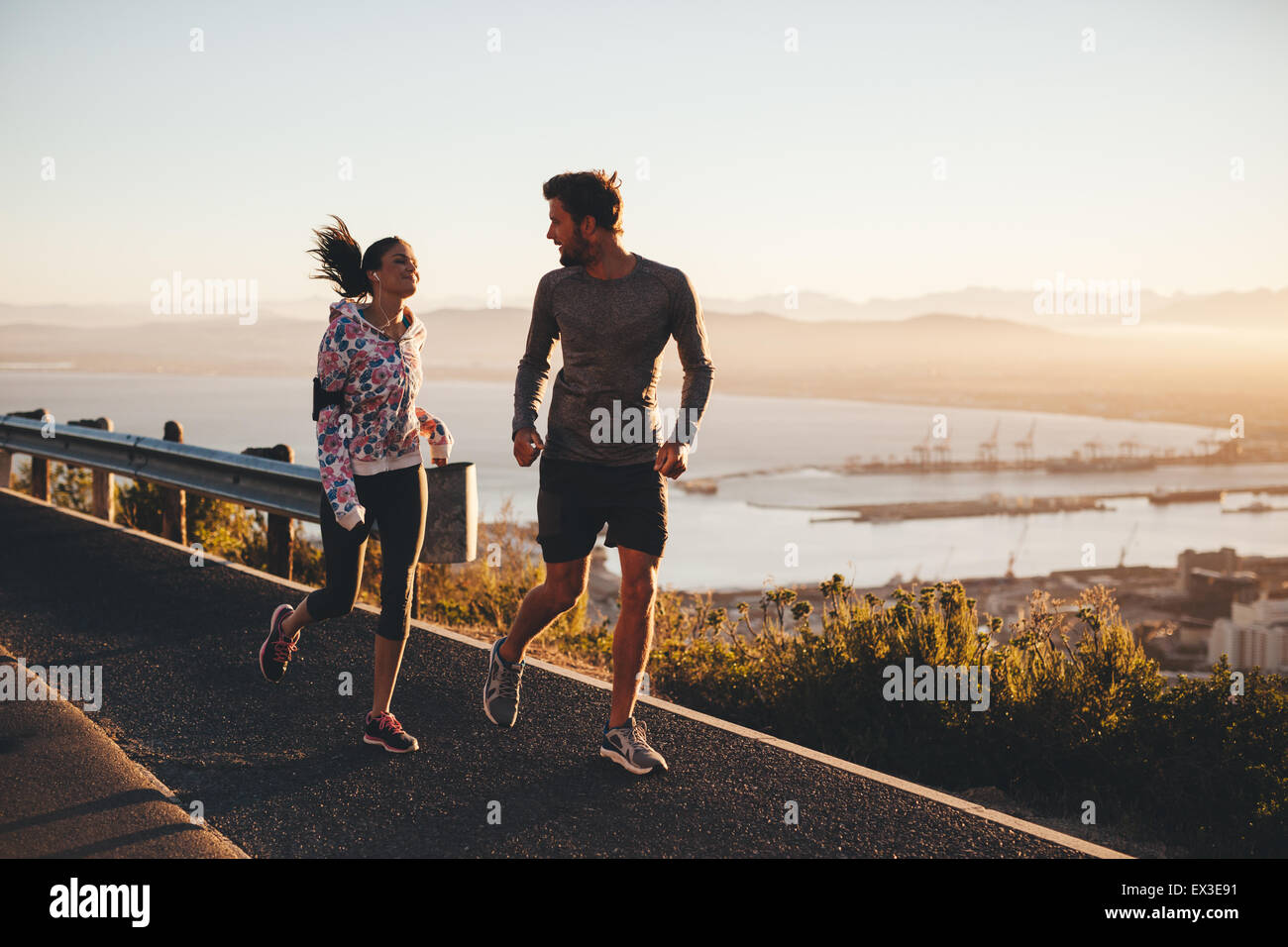 Shot of two people running on a country road in morning. Young man and woman jogging outdoors during sunrise. - Stock Image