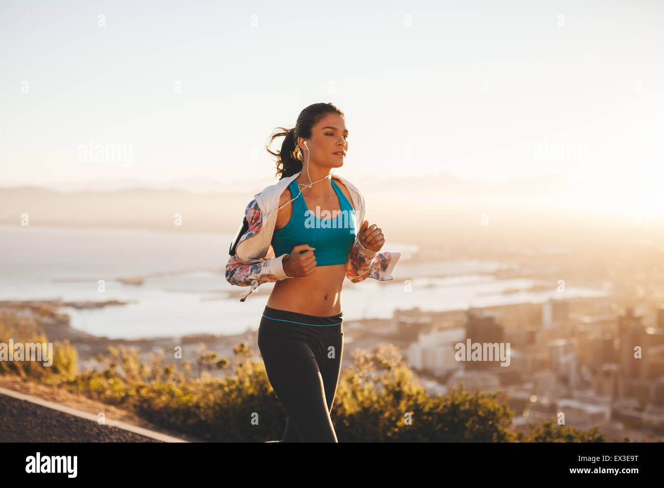 Fit young woman jogging outdoors. Female athlete on morning run with bright light. - Stock Image