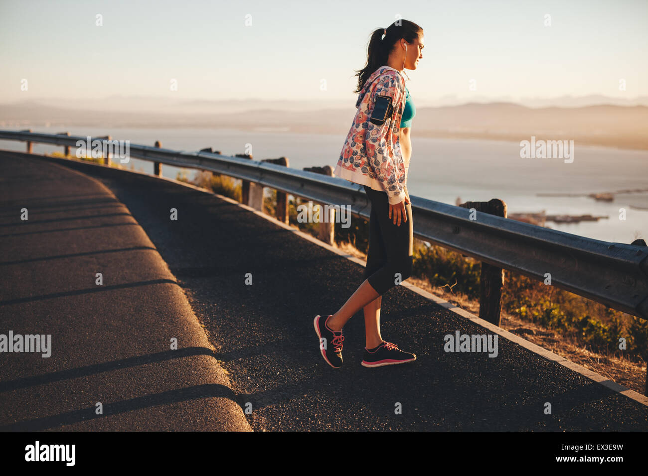 Shot of a young woman on running session standing on country road looking at a view. Fitness female athlete standing - Stock Image
