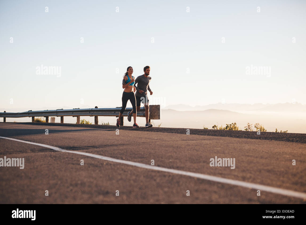 Outdoor shot of young couple on morning run. Young man and woman jogging on country road. - Stock Image