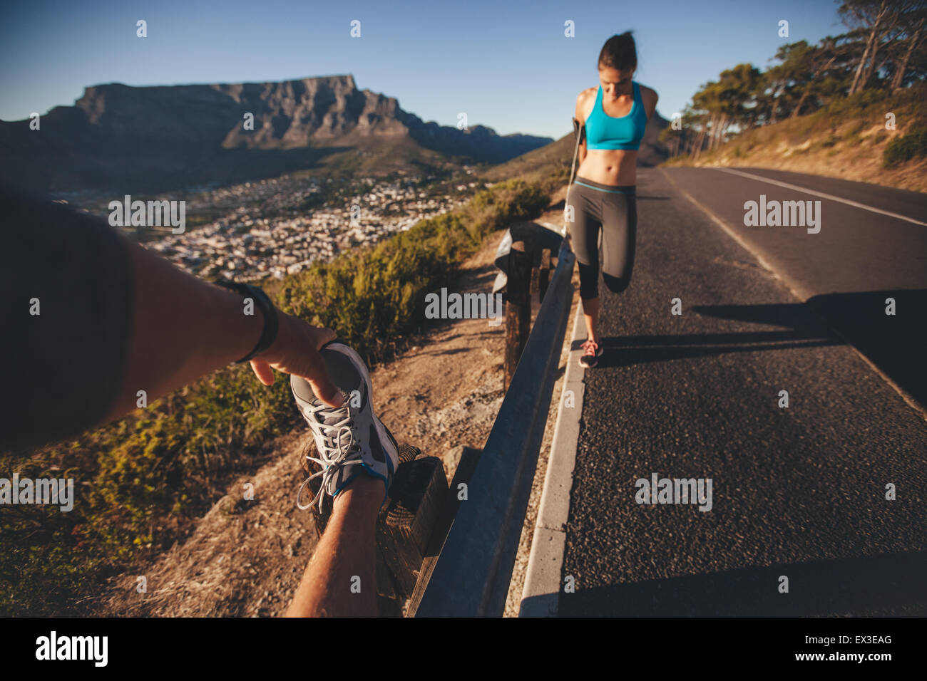 POV shot of man stretching his leg with woman exercising by a road guardrail. Young people relaxing their muscles - Stock Image