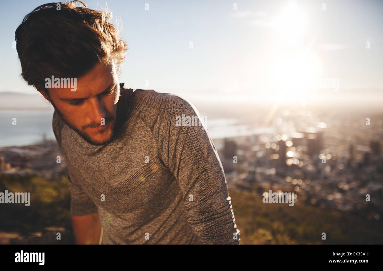 Close up shot of young man resting after running workout. Runner outdoors with bright sunlight. Athlete relaxing - Stock Image