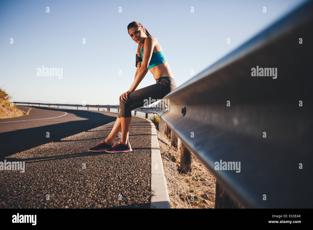 Tired young woman relaxing after a outdoor training session. Runner resting on road guardrail after morning run. - Stock Image