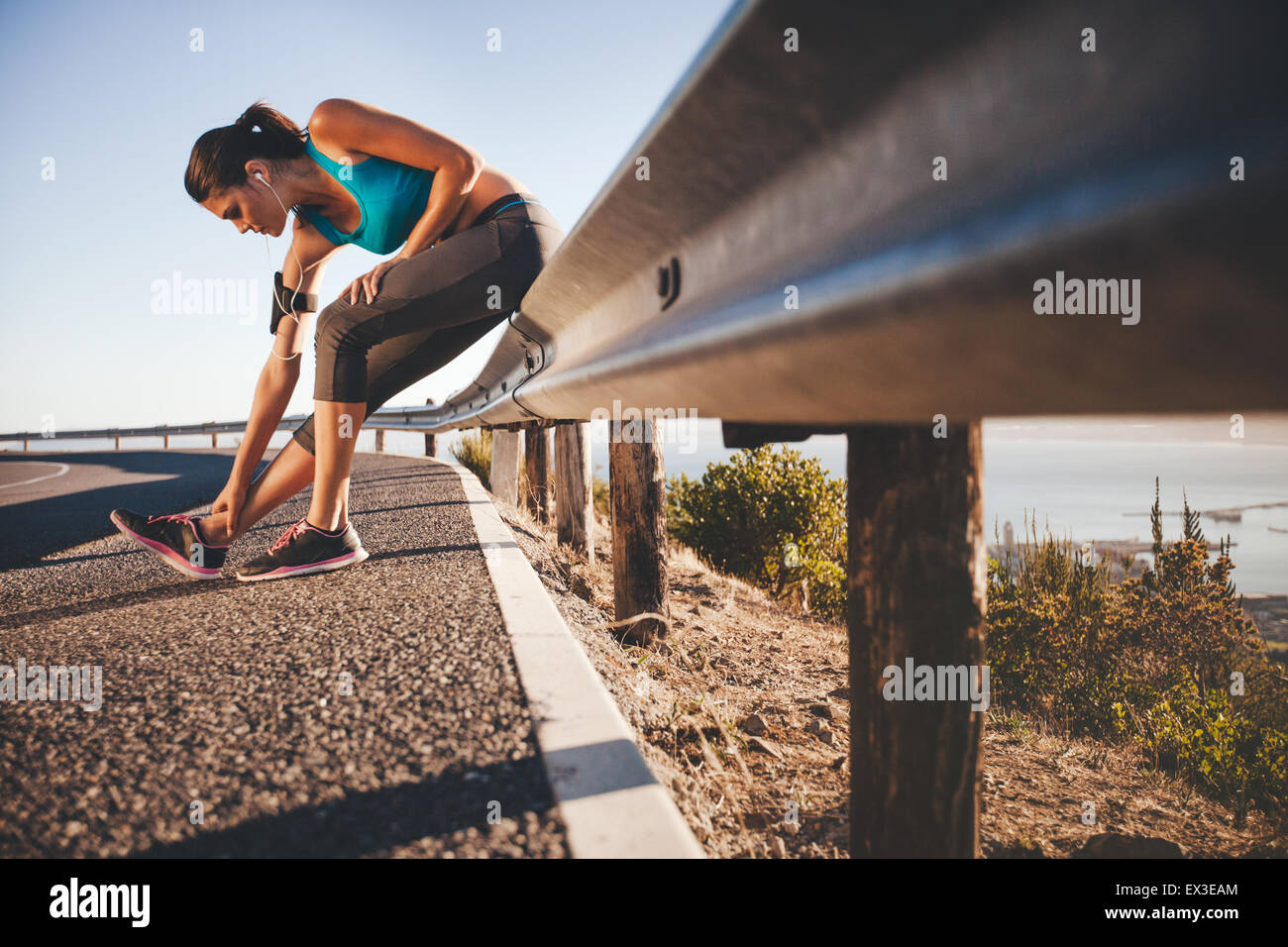 Sports woman stretching her leg after running outdoors. Female athlete taking break after running training sitting - Stock Image