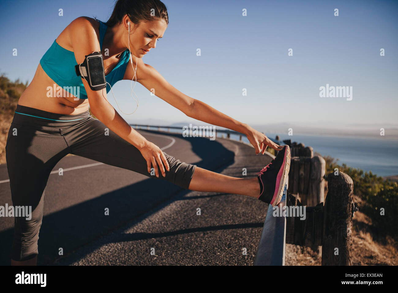 Female runner stretching her legs outdoor before running. Woman doing leg stretch exercises on road guardrail. - Stock Image
