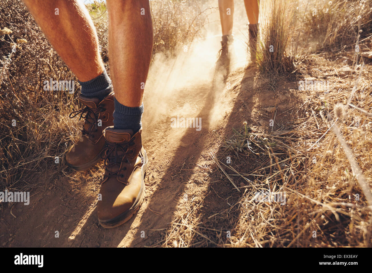 Low section shot of two young people walking on dirt trail, focus on men's hiking boots. Couple of hikers on - Stock Image