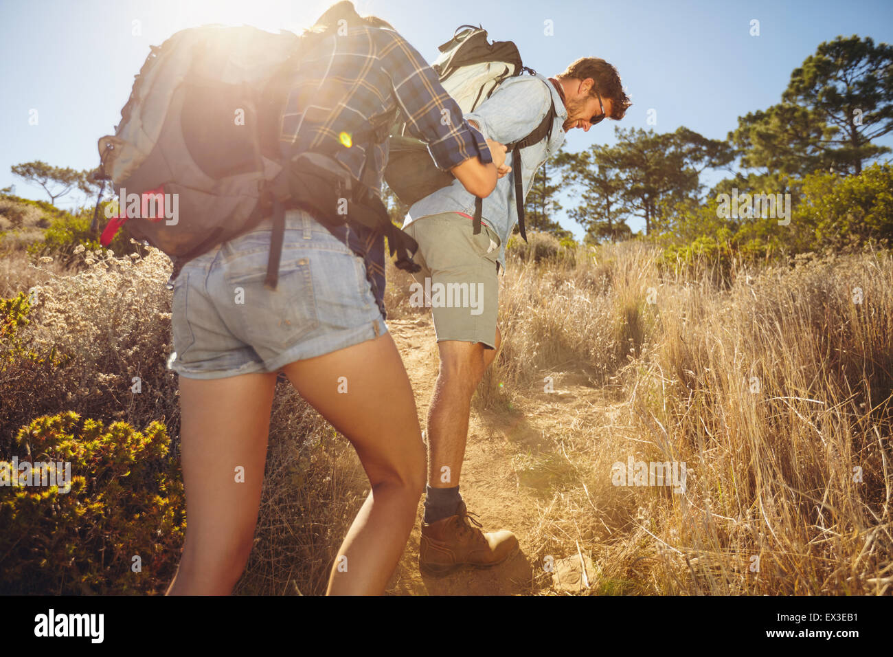 Hiker helping his girlfriend uphill in the countryside. Couple hiking in mountain on a summer day. - Stock Image