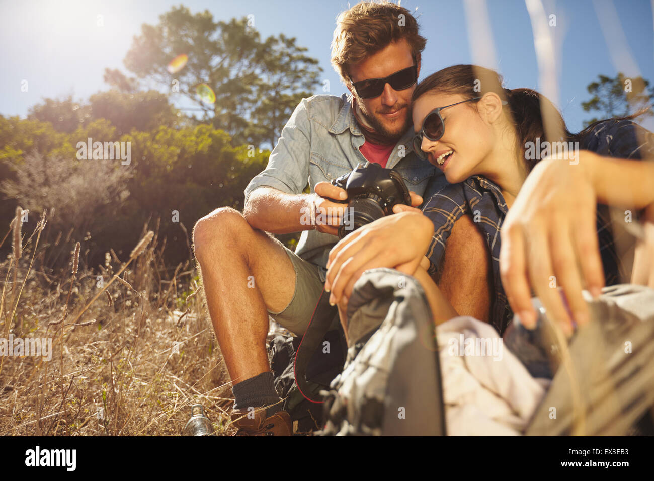 Outdoor shot of hiker couple looking at their camera on a summers day. Caucasian man and woman on hiking trip taking - Stock Image