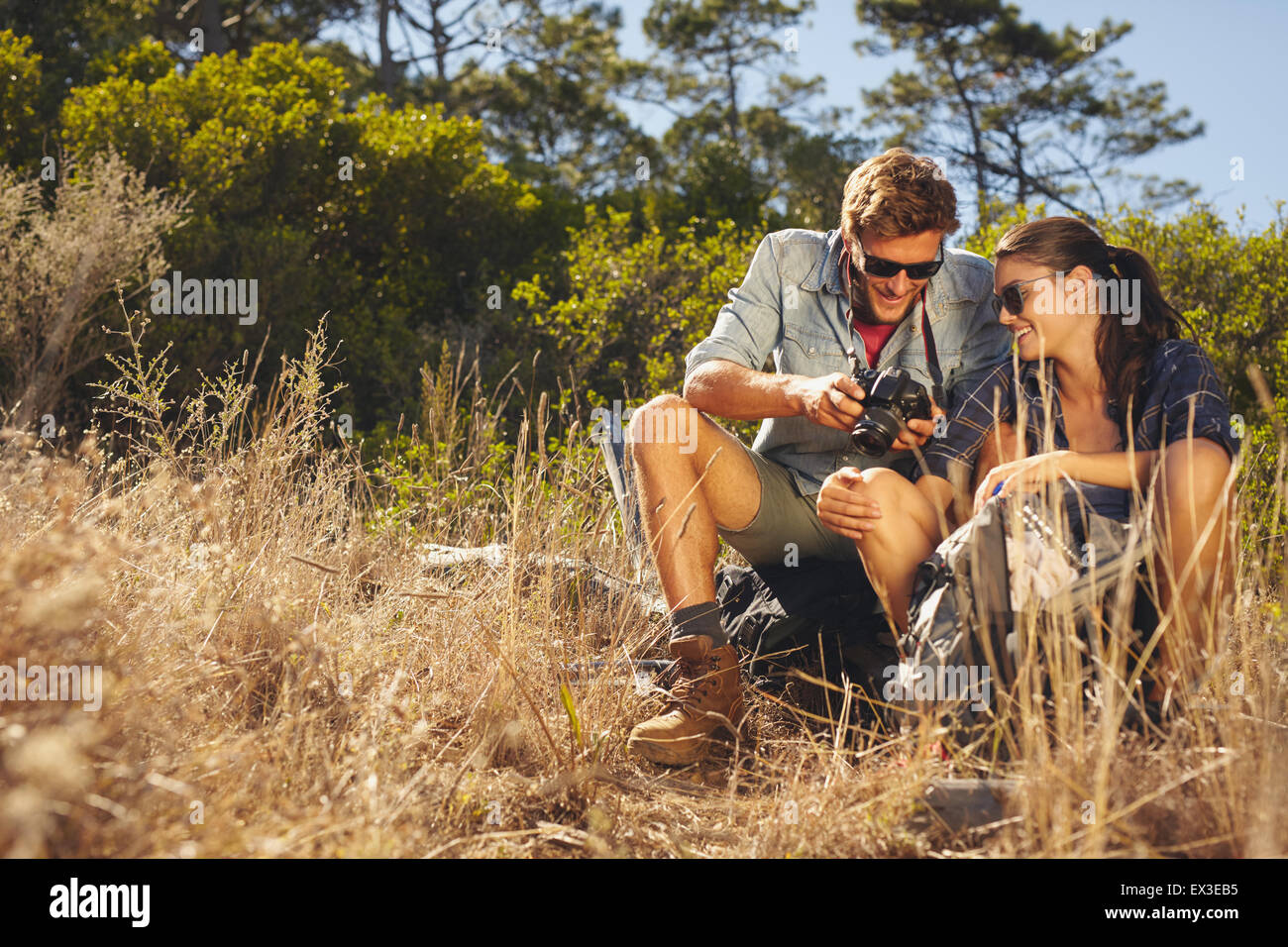 Young couple outdoors looking at photos on camera. Caucasian man and woman on hiking trip taking a break. - Stock Image