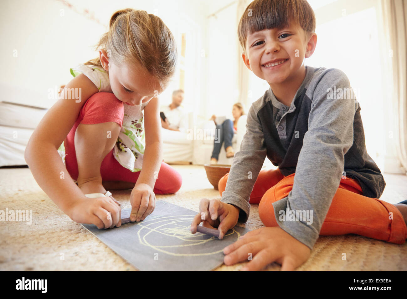 Indoor shot of happy little children drawing and coloring sitting on floor with parents in background at home - Stock Image