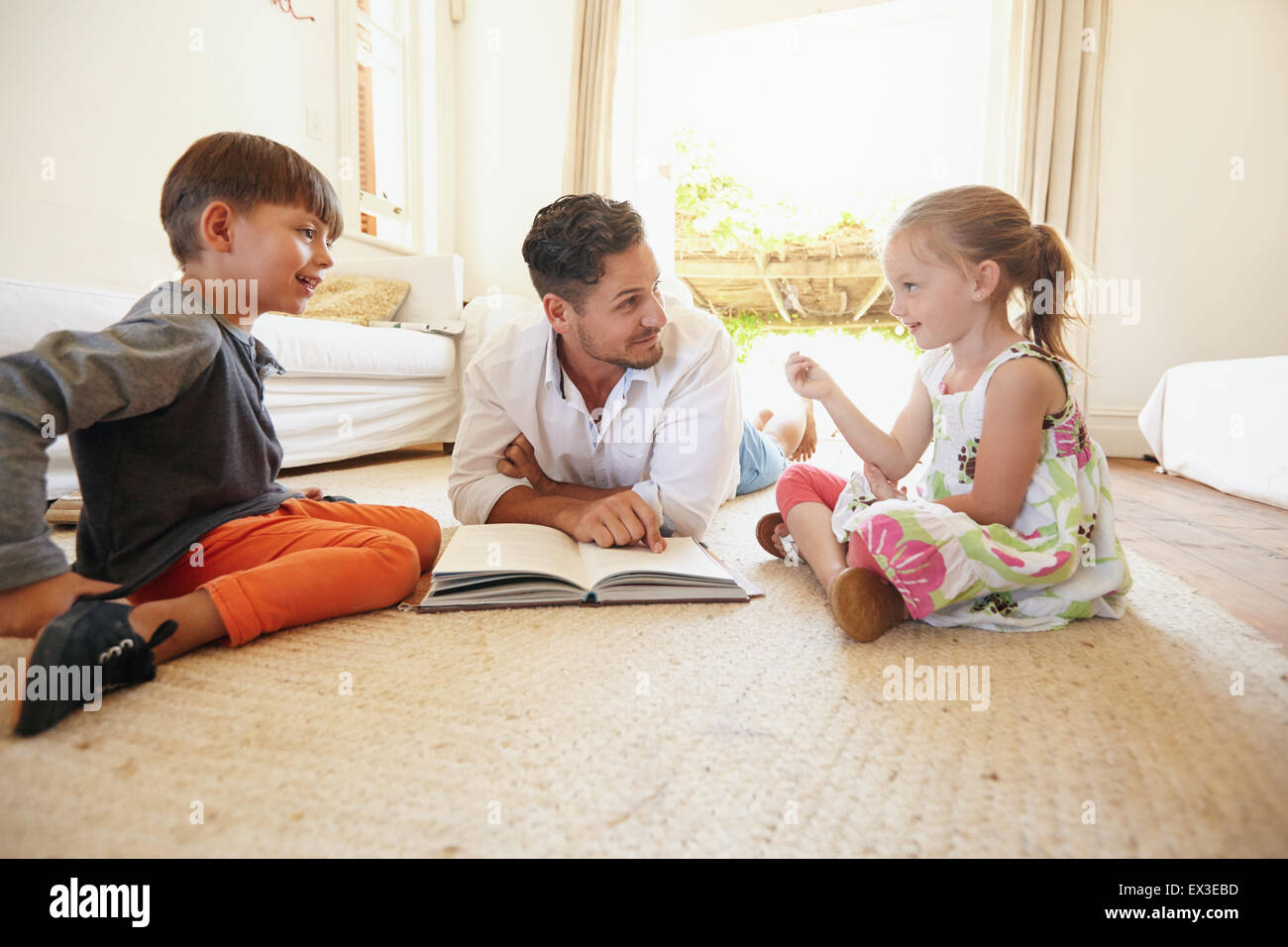 Family with book sitting on floor with little girl talking to his father and brother. Father with his little boy - Stock Image
