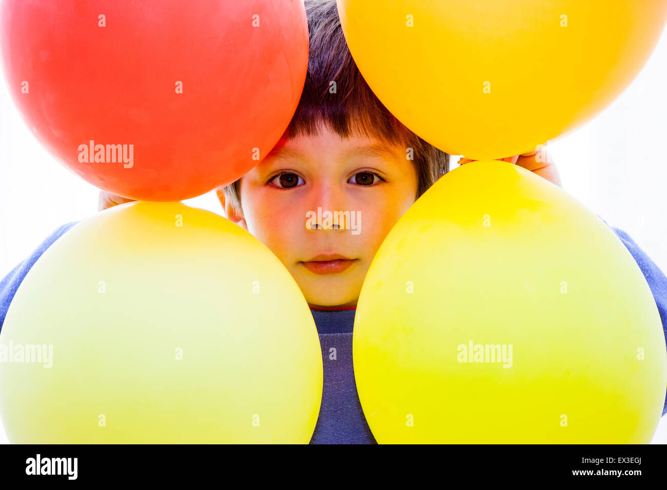 4 to 6 year old Caucasian boy, indoor. Face peeking through gap, surrounded by four balloons. Eye contact. - Stock Image