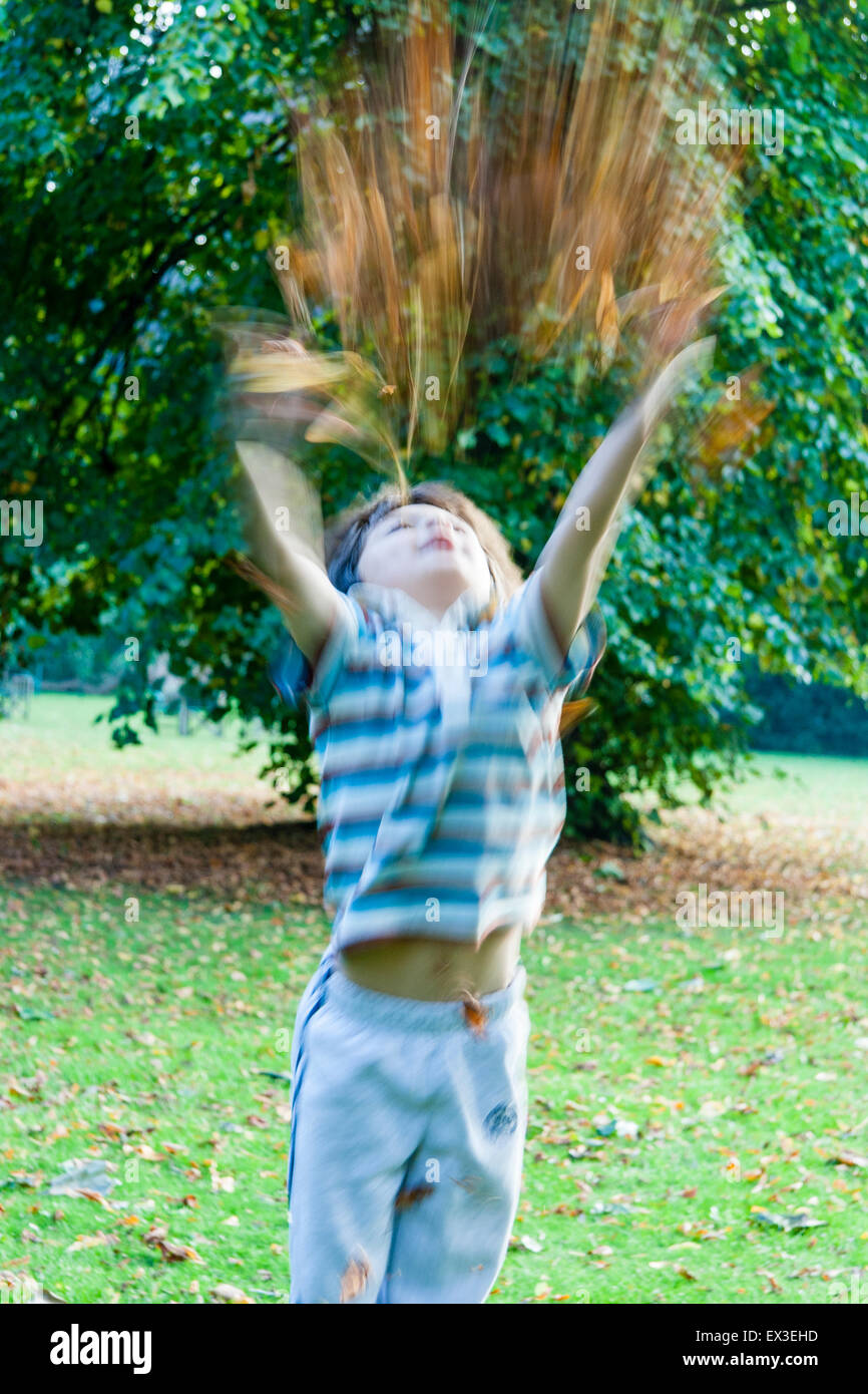 Boy, 7-8 year old, throwing armful of autumn leaves up into the air over his head. Caucasian child. Blurred motion. Stock Photo