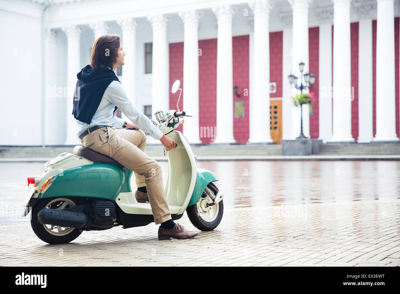 Man starts his scooter ready to drive the city - Stock Image