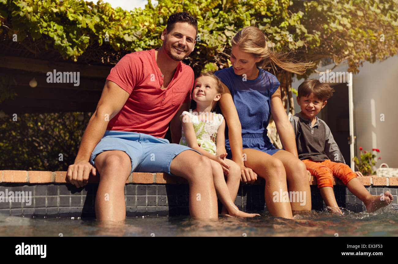 Outdoor shot of beautiful young family sitting next to swimming pool with their feet in water. Young couple with Stock Photo