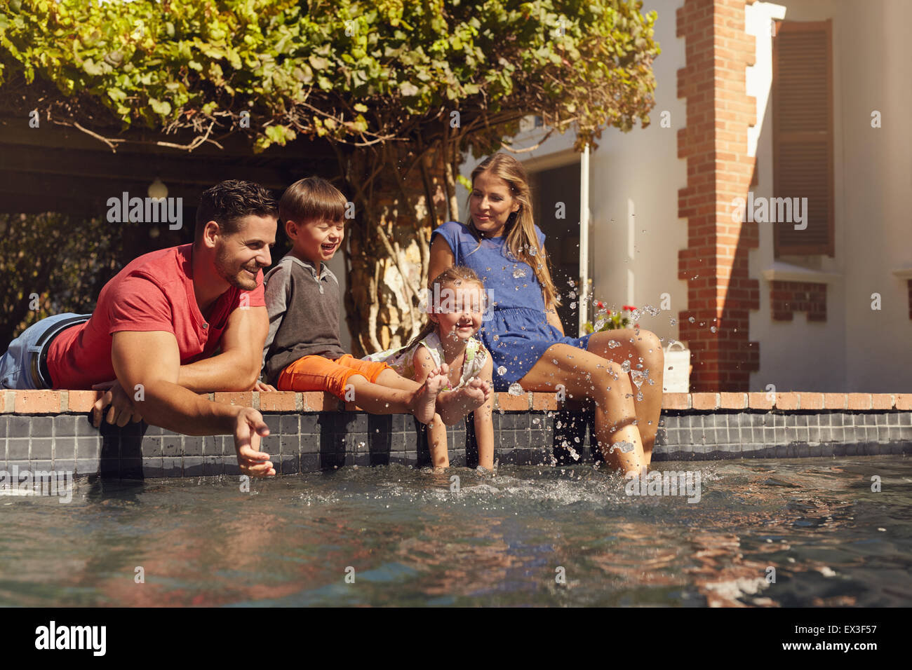 Outdoor shot of happy young family splashing water with hands and legs while sitting on edge of swimming pool. Family - Stock Image