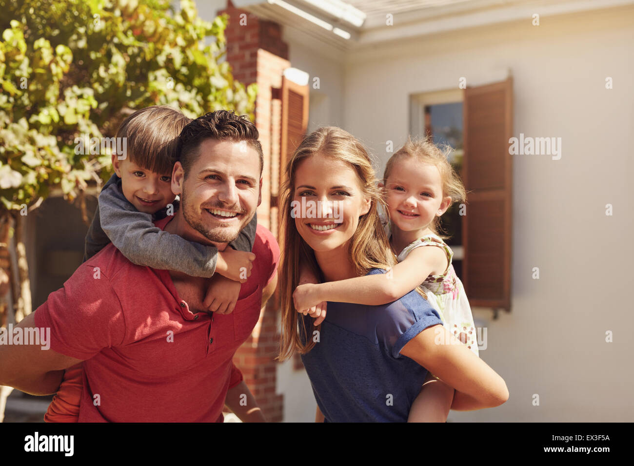 Portrait of a happy couple carrying their children on their backs. Parents giving their children piggyback rides - Stock Image