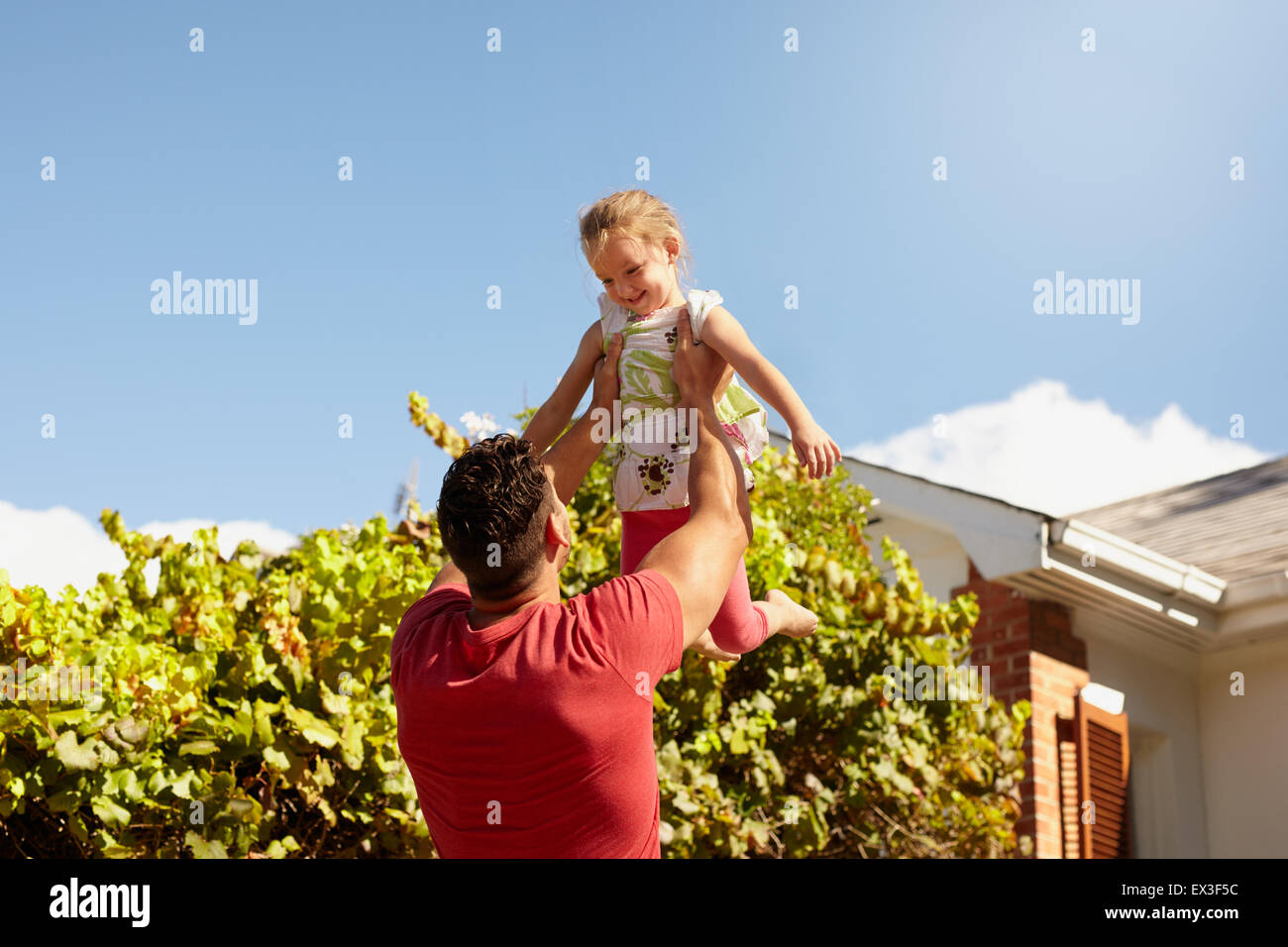Young man lifting his daughter high in the air. Happy father and daughter playing in their backyard on a sunny day. - Stock Image