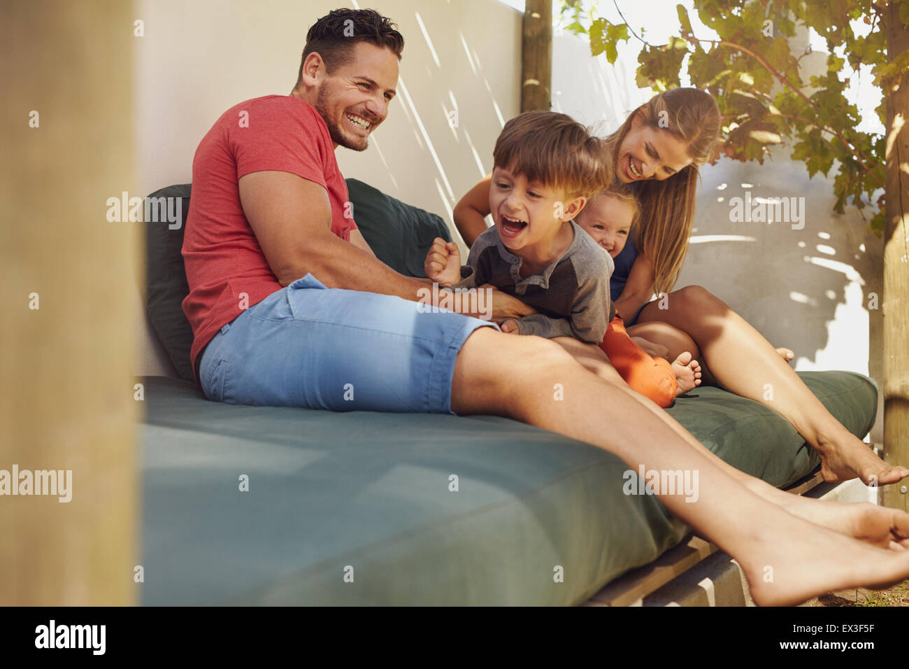 Happy family sitting together in the backyard, having fun. Father and mother playing with their kids while sitting - Stock Image