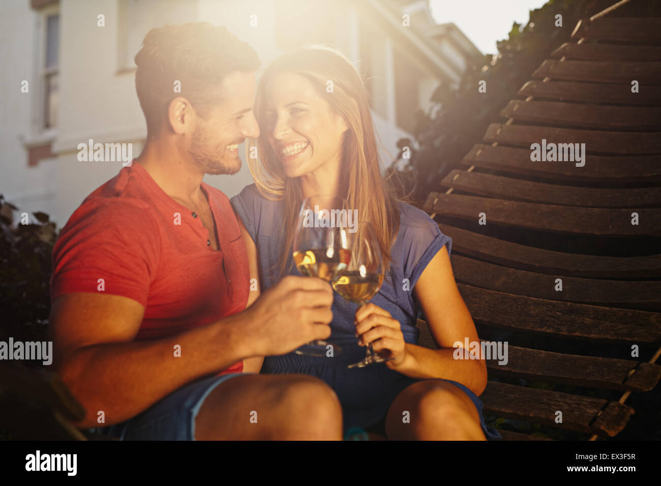 Happy young couple sitting on hammock toasting wine and looking at each other smiling. Loving young couple relaxing - Stock Image