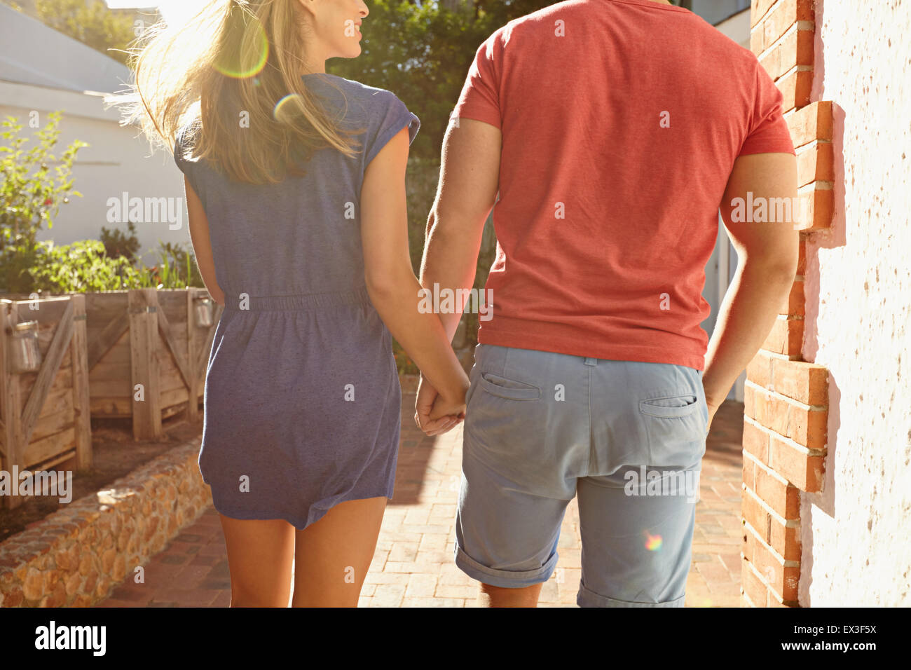 Rear view shot of a young couple holding hands taking a walk outside in their backyard. Cropped shot of young couple - Stock Image