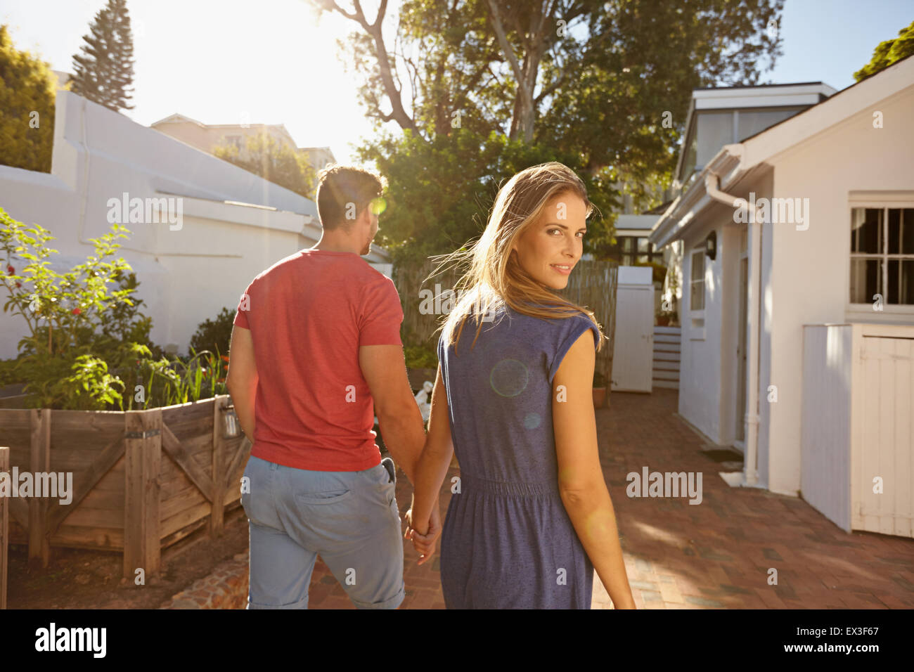 Young couple walking in the backyard holding hand in hand on a bright summer day, with woman looking back over shoulder - Stock Image