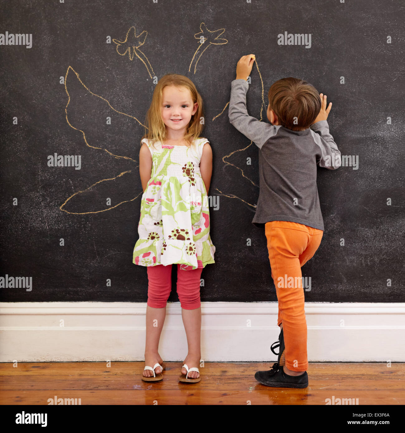 Full length portrait of cute little girl standing and little boy drawing angel wings around her on blackboard. - Stock Image
