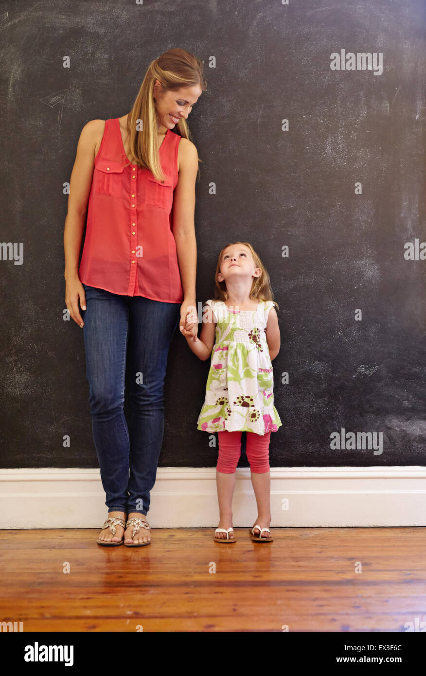 Full length shot of sweet little girl standing with her mother at home. Mother and daughter looking at each other - Stock Image
