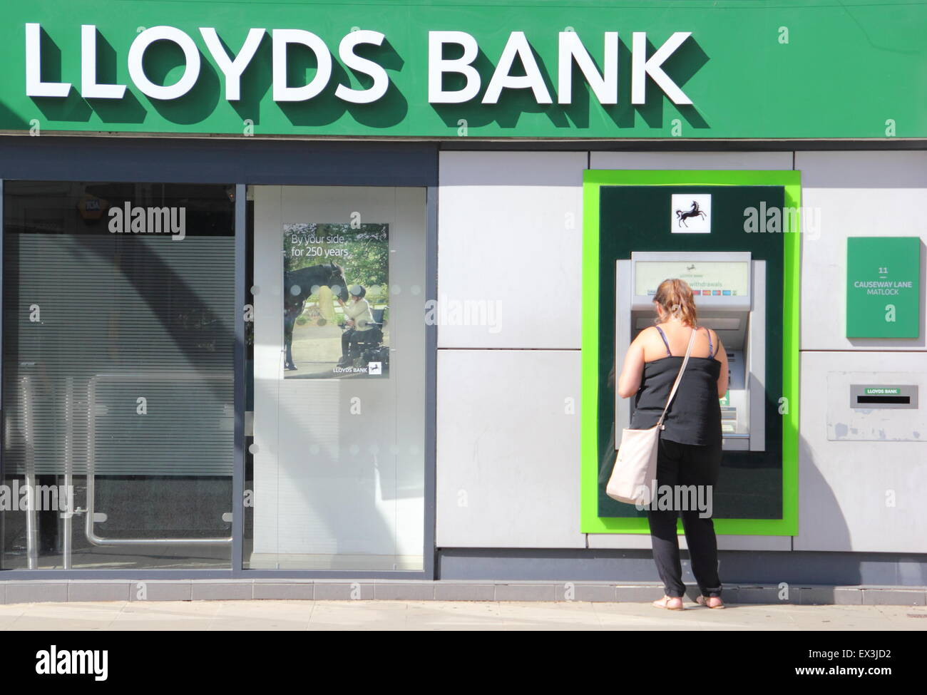 A woman uses an ATM cashpoint machine at a Lloyds Bank branch in Derbyshire England UK - Stock Image