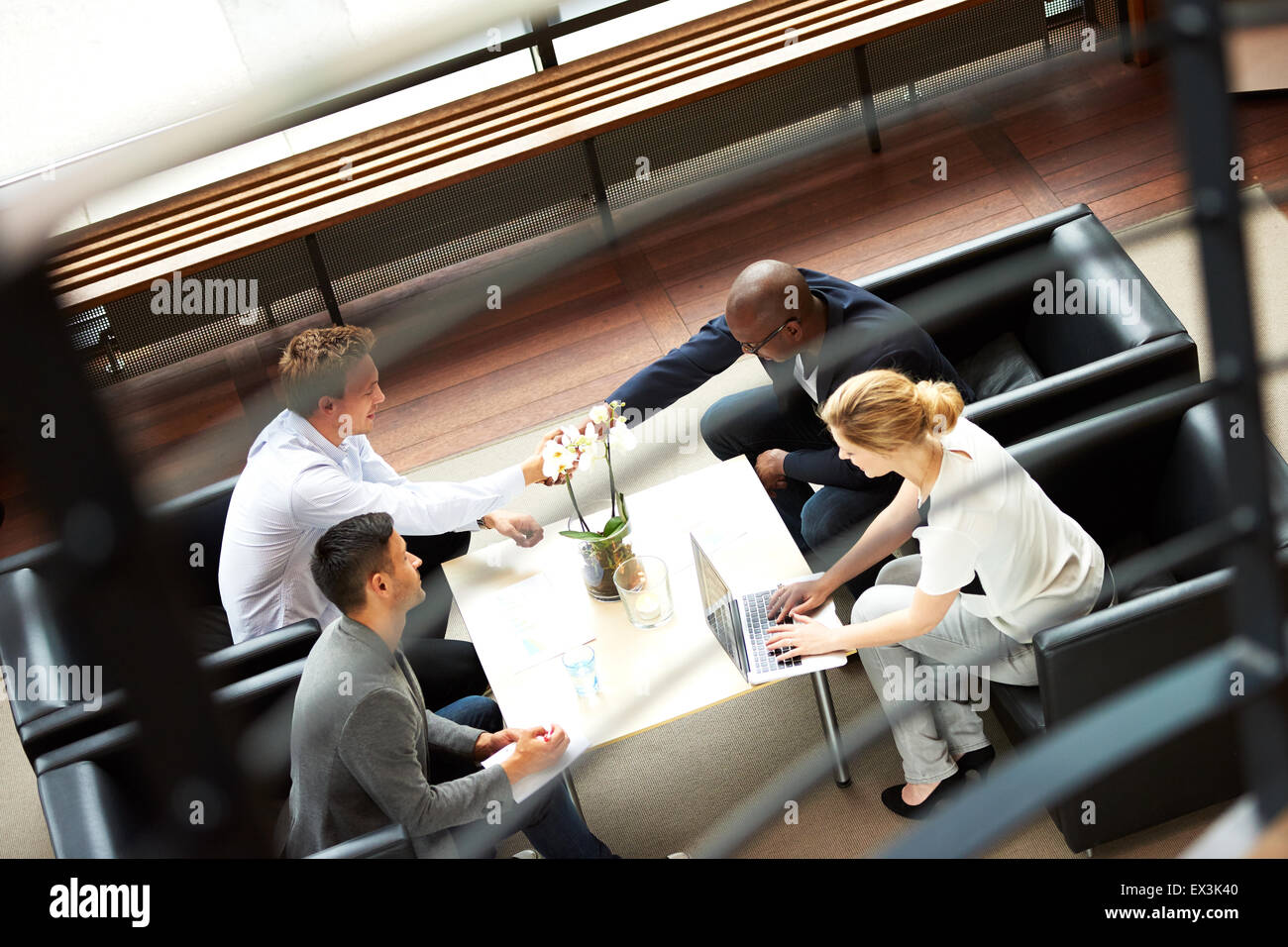 Black man and white man shaking hands during work meeting in modern office. - Stock Image