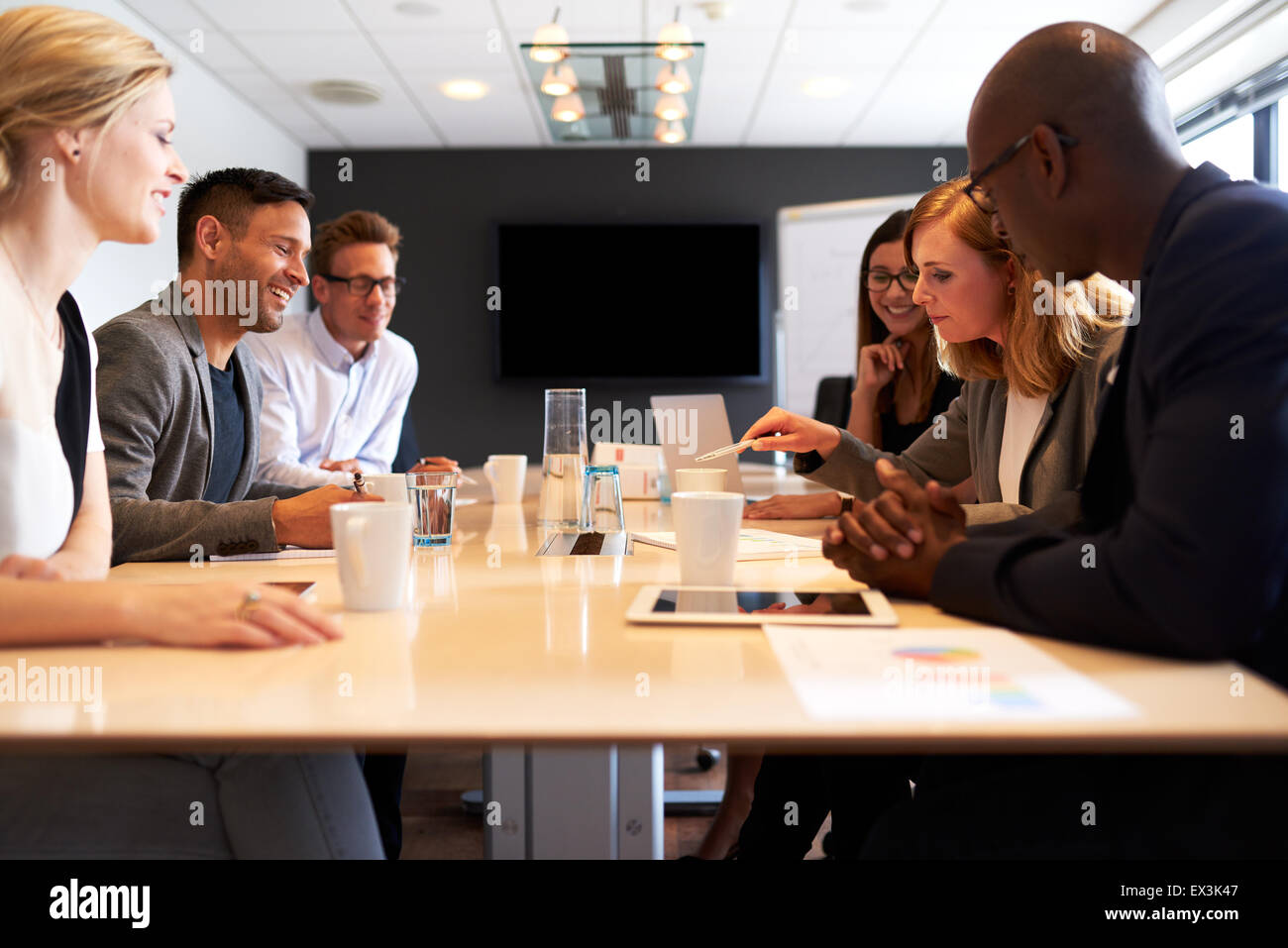 Group of young executives having a meeting in a conference room - Stock Image