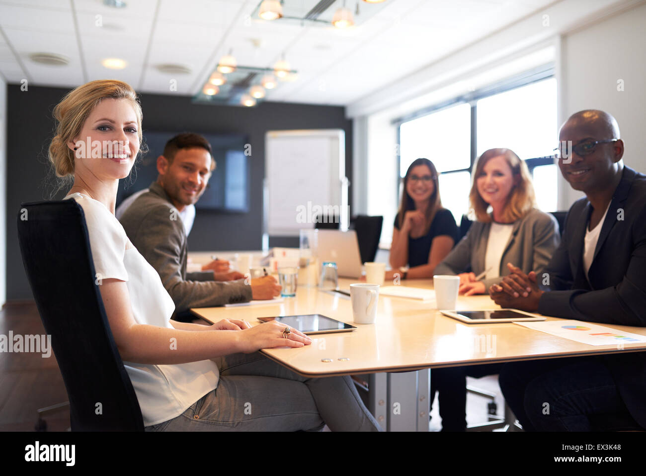 Group of young executives smiling at camera during a work meeting. - Stock Image